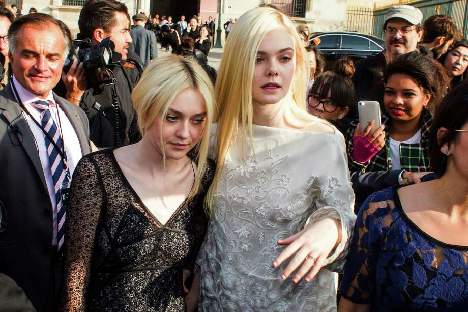Looking a little exhausted - Dakota Fanning, left, and her sister Elle Fanning, leave after attending the presentation of Vuitton's ready-to-wear Spring/Summer 2014 fashion collection, presented Wednesday, Oct. 2, 2013 in Paris. Photo: AP