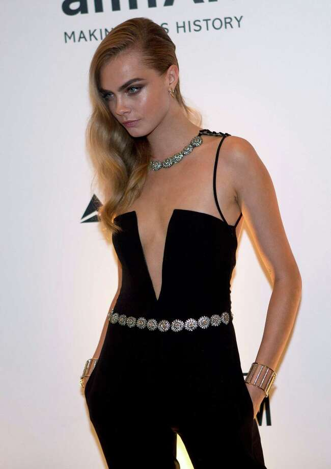 British model Cara Delevingne poses for photographers as she arrives to a charity dinner for amfAR, a foundation for AIDS research in Rio de Janeiro, Brazil, Friday, Oct. 4, 2013. Photo: AP