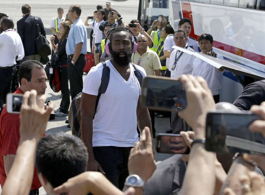 Fans take photos of Rockets guard James Harden while he waits to get on the bus. Photo: Bullit Marquez, Associated Press