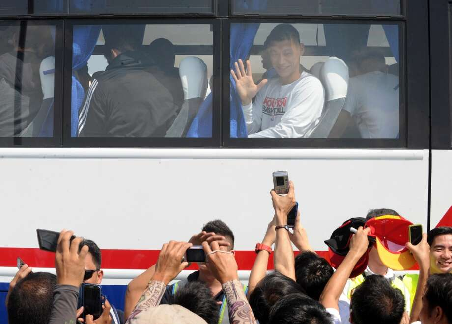 Jeremy Lin waves to fans after boarding the bus. Photo: Jay Directo, AFP/Getty Images