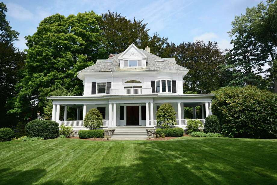The circa-1900 Colonial  at 66 Pear Tree Point Road in Darien begins with a grand, twisting driveway that curves and climbs up to the house on a hill. It is on the market for $5,150,000. Photo: Contributed