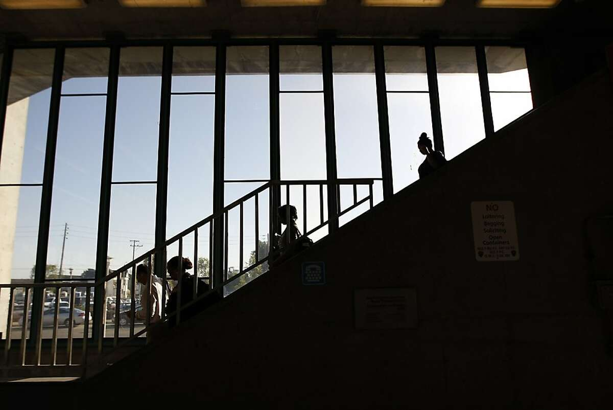 People walk down the stairs at the West Oakland BART station in West Oakland, California Wednesday October 2, 2013.