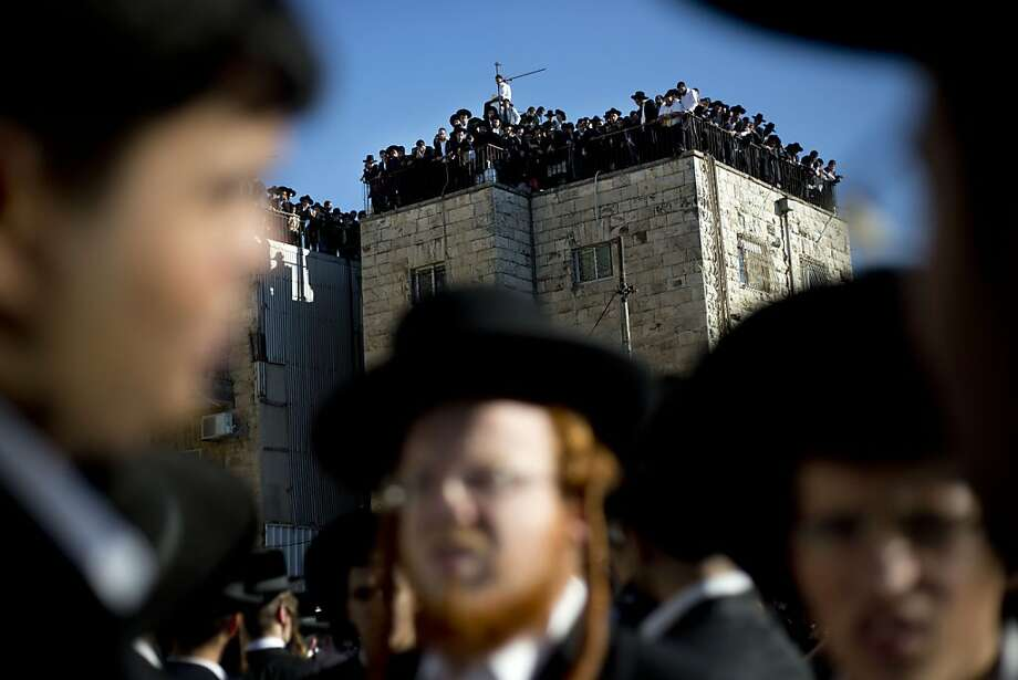 Orthodox Jews gather to watch the funeral procession of Rabbi Ovadia Yosef in Jerusalem, Monday, Oct. 7, 2013. Rabbi Yosef, the religious scholar and spiritual leader of Israel's Sephardic Jews who transformed his downtrodden community of immigrants from North Africa and Arab nations and their descendants into a powerful force in Israeli politics, has died. He was 93.(AP Photo/Ariel Schalit) Photo: Ariel Schalit, Associated Press