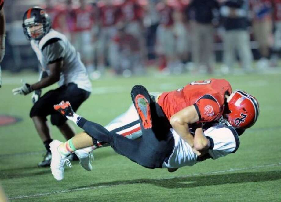 New Canaan's Cole Harris, top, lays-out Fairfield Warde running back Matt Kerigan.Photo/Bob Luckey