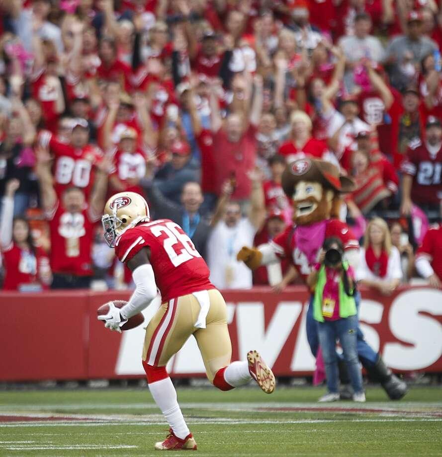 49ers defensive back Tramaine Brock returns an intercepted pass by Texans quarterback Matt Schaub 18 yards for a touchdown during the first quarter. Photo: Brett Coomer, Houston Chronicle