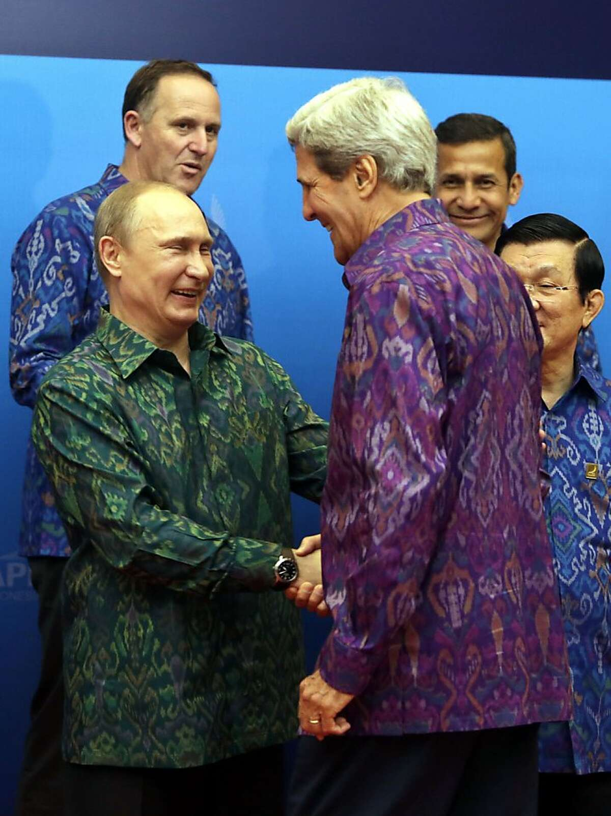Thank you for coming to my '60s party, Mr. Secretary: Russia's President Vladimir Putin shakes hands with Secretary of State John Kerry before a gala dinner for the leaders at the Asia-Pacific Economic Cooperation Summit in Nusa Dua, Bali.