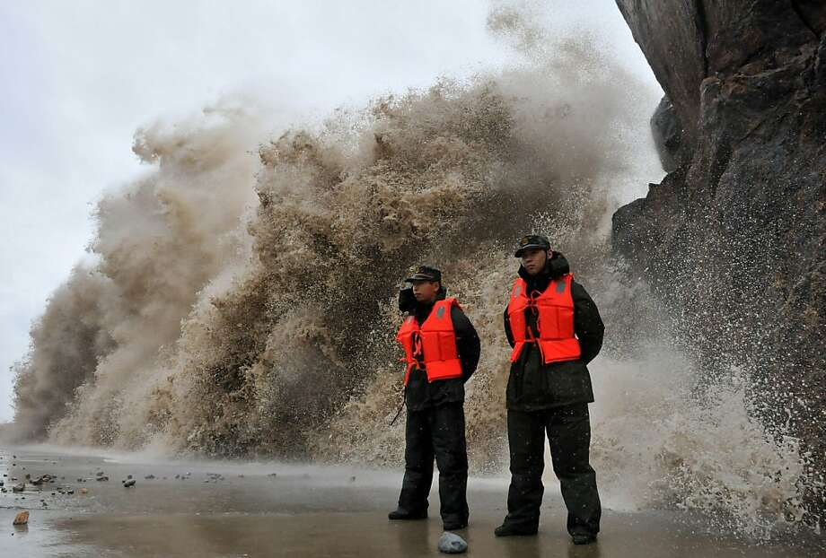 When do we stop guarding and start fleeing? A huge wave breaks against a dike in Wenling, China, as Typhoon Fitow approaches. Tens of thousands of people on China's east coast were evacuated ahead of the storm. Photo: Stringer, AFP/Getty Images