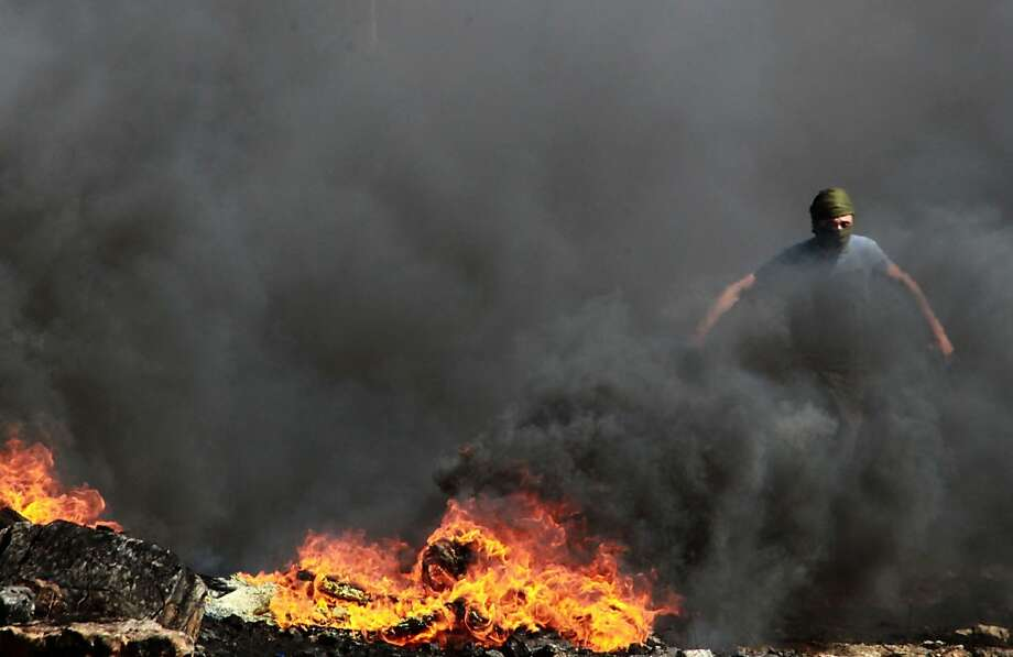 TOPSHOTS A Palestinian stone thrower runs by burning tires during clashes with Israeli soldiers following a demonstration against the expropriation of Palestinian land by Israel on October 4, 2013 in the village of Kfar Qaddum, near the occupied West Bank city of Nablus. TOPSHOTS/AFP PHOTO / JAAFAR ASHTIYEHJAAFAR ASHTIYEH/AFP/Getty Images Photo: Jaafar Ashtiyeh, AFP/Getty Images