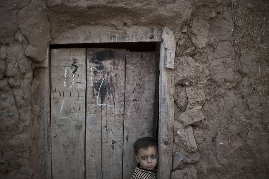An Afghan child stands in the doorway of his home in a poor neighborhood outside Islamabad. Pakistan 