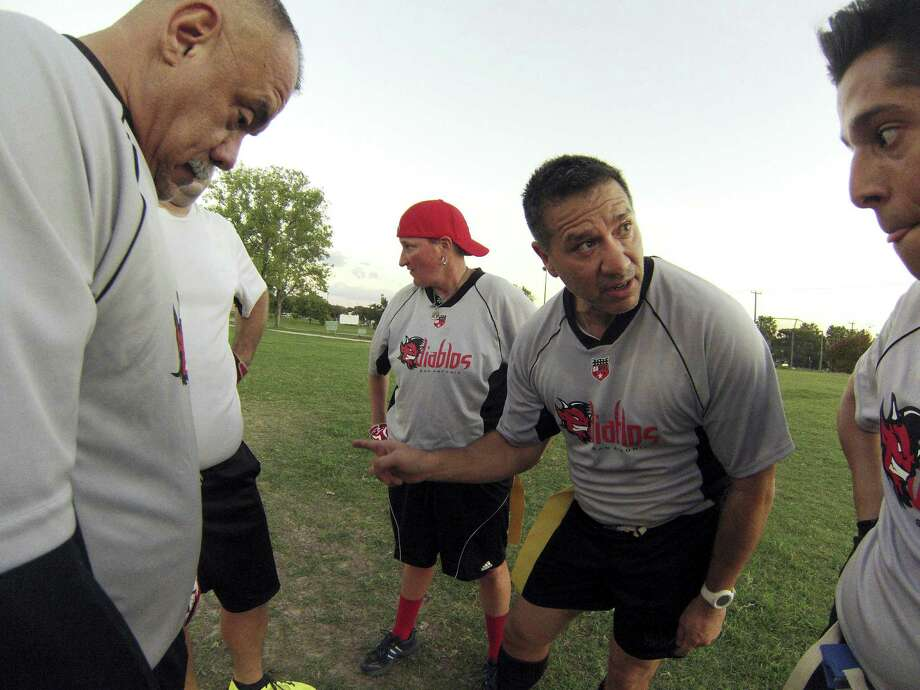 Quarterback Pablo Cruz calls a play for teammates Bob Cervantes (from left), Ginger Daniel and Saul Ramirez during a workout of the San Antonio Diablos, the traveling team of the San Antonio Gay Flag Football League. The league is open to gay, straight, bisexual and transgender men and women. Photo: Photos By Billy Calzada / San Antonio Express-News