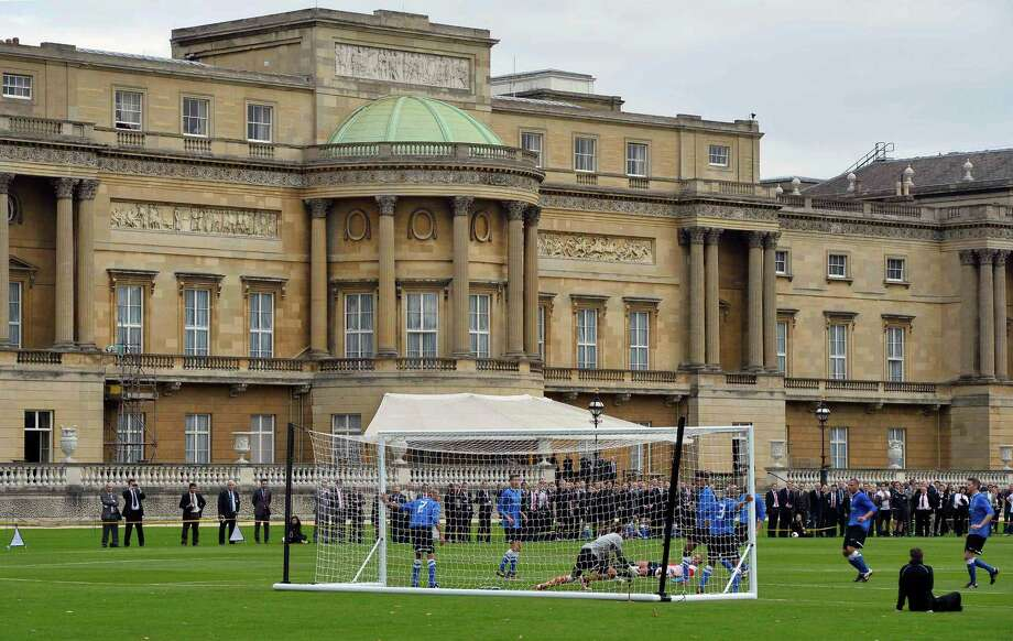 Polytechnic FC (in blue), during their match with the Civil Service FC in Buckingham Palace's garden, central London Monday Oct. 7, 2013. The Duke of Cambridge, president of the FA, helped organise the event, the first of its kind at Queen Elizabeth II's London home, as part of the Football Association's 150th anniversary celebrations. (AP Photo/ Toby Melville, Pool) ORG XMIT: LON108 Photo: Toby Melville / Pool Reuters