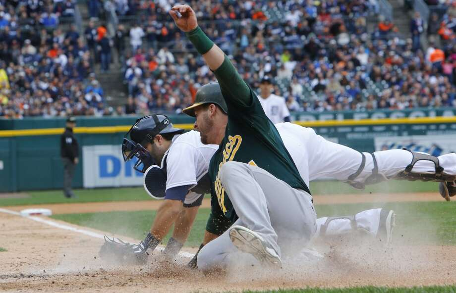 Oakland Athletics' Stephen Vogt safely beats the tag of Detroit Tigers catcher Alex Avila to scoree during the fourth inning of Game 3 of an American League baseball division series in Detroit, Monday, Oct. 7, 2013. Photo: Paul Sancya, Associated Press