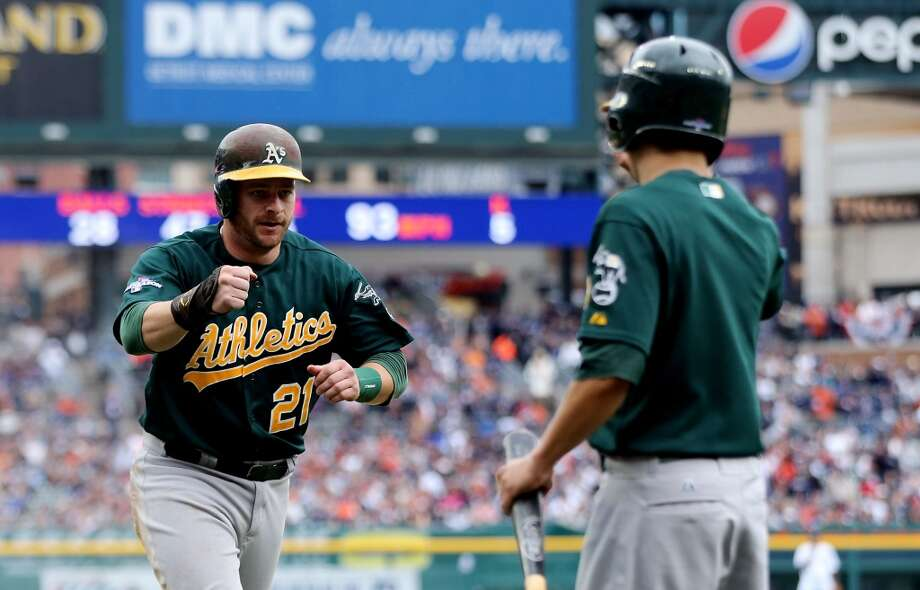 Stephen Vogt returns to the dugout after scoring against the Detroit Tigers during Game Three of the American League Division Series at Comerica Park. Photo: Leon Halip, Getty Images
