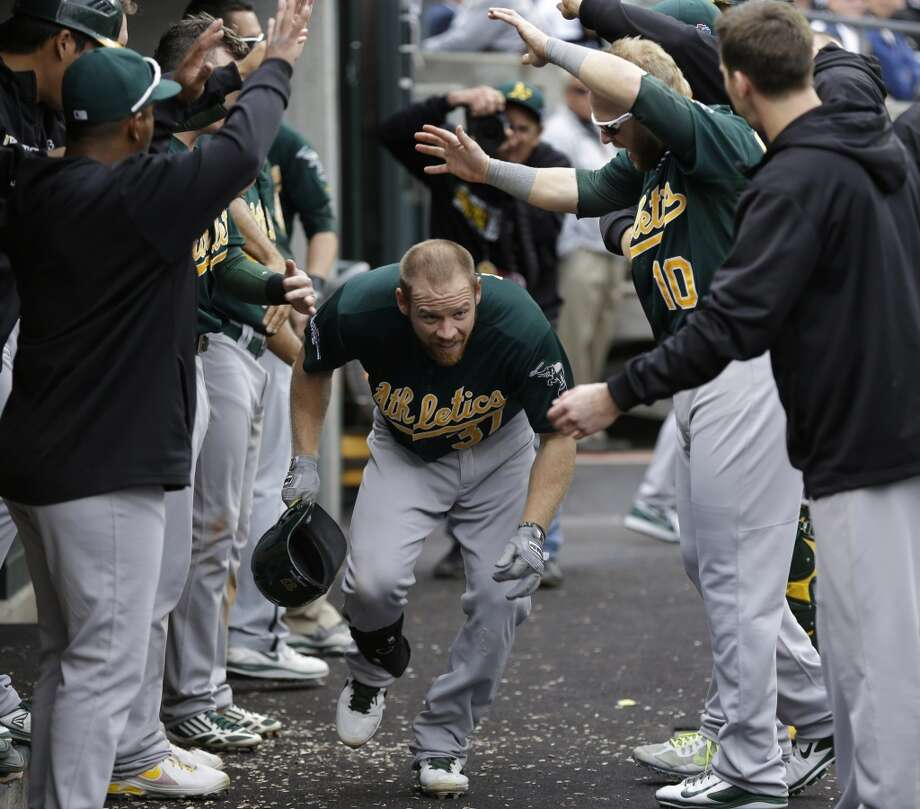 Oakland Athletics' Brandon Moss is cheered by teammates after his solo home run during the fifth inning. Photo: Paul Sancya, Associated Press