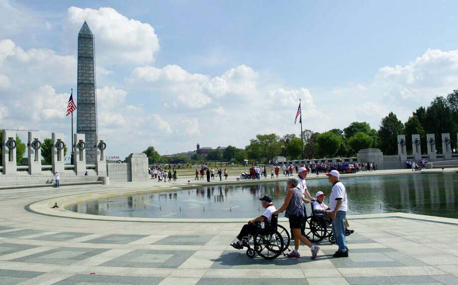 "American war veterans visit the ""closed"" World War II Memorial on Saturday in Washington, D.C. Veterans continue to make their pilgrimages there despite the government shutdown. Photo: Karen Bleier / AFP / Getty Images"