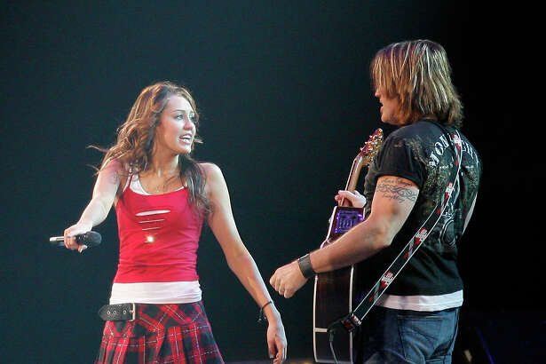 Miley Cyrus, also performing as Hannah Montana performs with her father, Billy Ray Cyrus at the 2008 Houston Livestock Show and Rodeo featuring Hannah Montana at Reliant Stadium.  (Sunday, March 9, 2008, in Houston. ( Steve Campbell / Houston Chronicle)