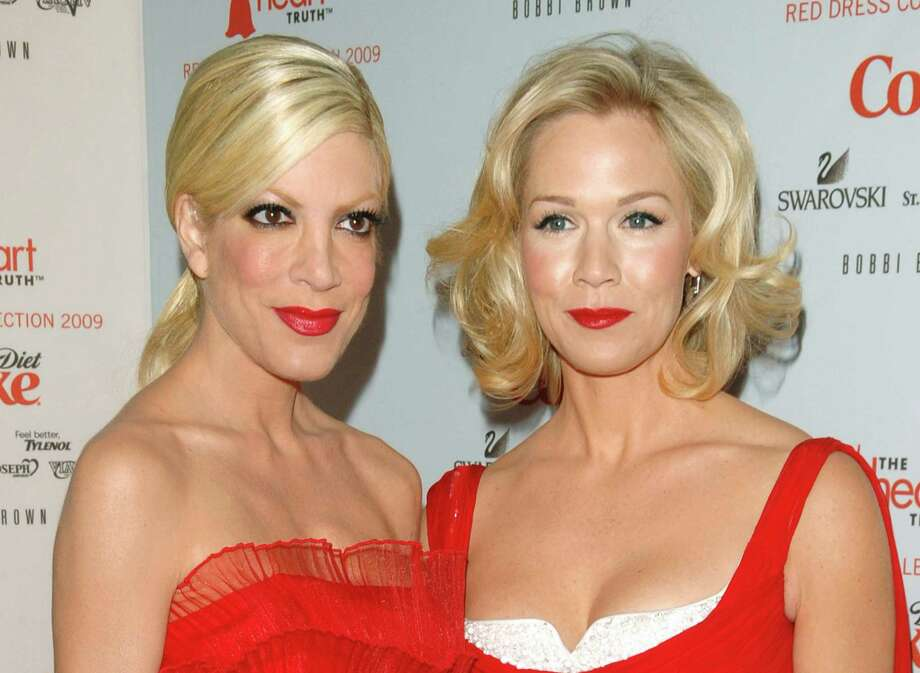 "FILE - This Feb. 13, 2009 file photo shows actors Tori Spelling, left, and Jennie Garth at the Heart Truth's Red Dress collection during Fashion Week in New York. Former ""Beverly Hills, 90210"" stars Jennie Garth and Tori Spelling are reuniting. The actresses will co-star and executive produce the new ABC Family series ""Mystery Girls."" In the series, Spelling and Garth play Holly and Charlie, who were on a crime-solving series in the 90's that was the highest-rated show on TV. Spelling's Holly is looking to reignite her fame and opens a detective agency. She persuades Charlie, now a suburban mom to help. ""Mystery Girls"" is set to shoot in November. (AP Photo/Peter Kramer, File) ORG XMIT: NYET131 Photo: Peter Kramer / KRAPE"