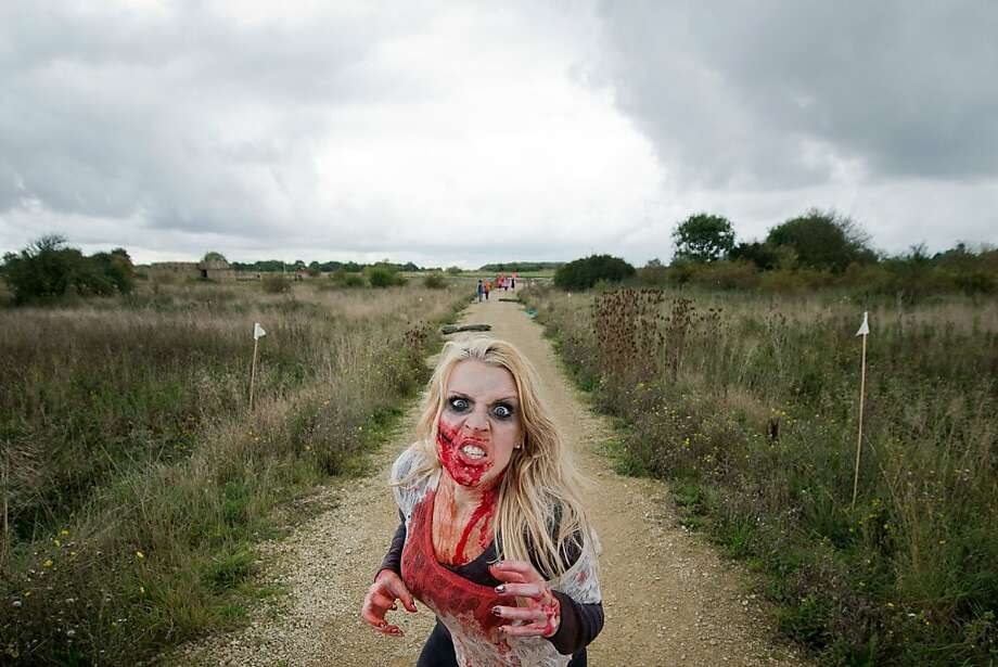 "For volunteer zombies, chasing the living is its own reward:A ""volunteer zombie"" waits to ambush cross-country runners during the Zombie Evacuation Race near Saffron Walden, England. Thousands of competitors attempt to complete the grueling 5k race while evading zombies who try to snatch three life-line strips hanging from each runner's waist. Those who get through with any strips remaining are named survivors. Photo: Leon Neal, AFP/Getty Images"
