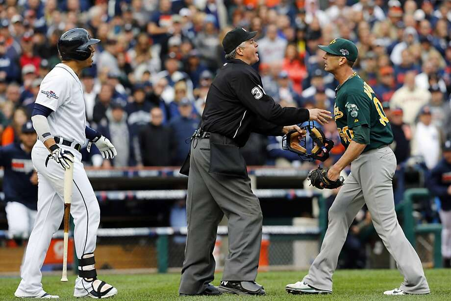 Home plate ump Gary Darling stands between the A's Grant Balfour (right) and Detroit's Victor Martinez. Photo: Paul Sancya, Associated Press