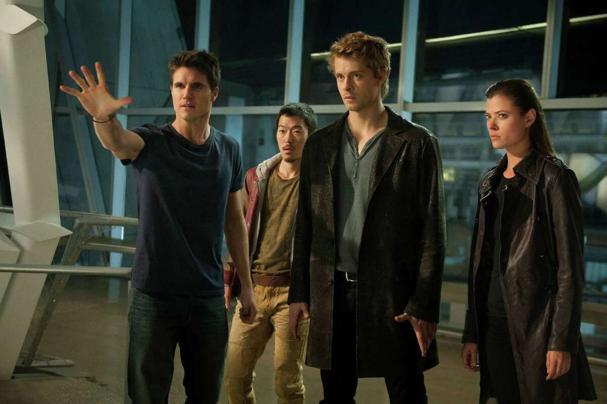 """This image reelased by The CW shows, from left, Robbie Amell as Stephen, Aaron Woo as Russell, Luke Mitchell as John and Peyton List as Cara in a scene from """"The Tomorrow People,"""" premiering on Wednesday, Oct. 9. (AP Photo/The CW,Barbara Nitke)"""