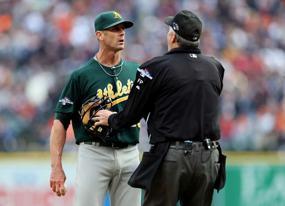 Grant Balfour is held back by home plate umpire Gary Darling after exchanging words with Victor Martinez. Photo: Rob Carr, Getty Images