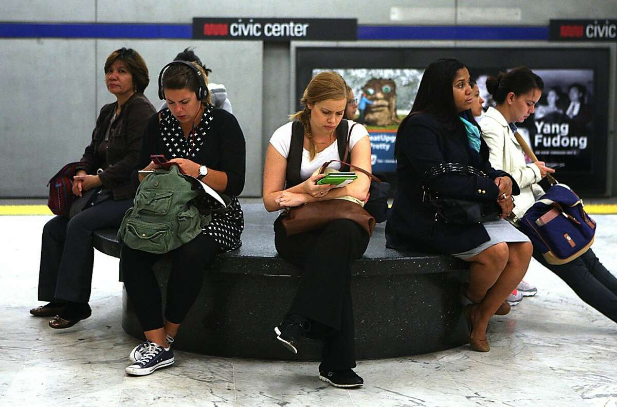 Passengers wait for the Muni train at the civic center station in San Francisco, California, while using their phones on Friday, October 4, 2013.