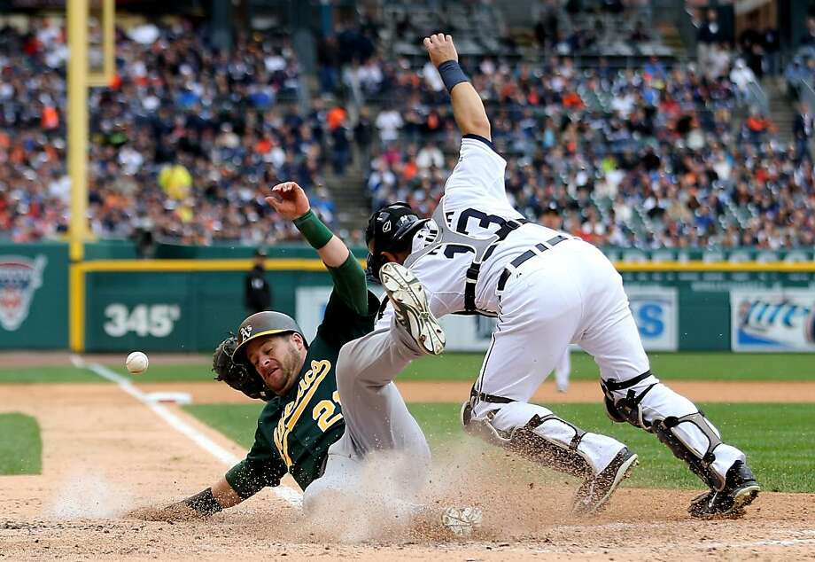 A's catcher Stephen Vogt slides home safely after Coco Crisp's flyball to left allowed him to tag up in the fourth inning. Photo: Leon Halip, Getty Images