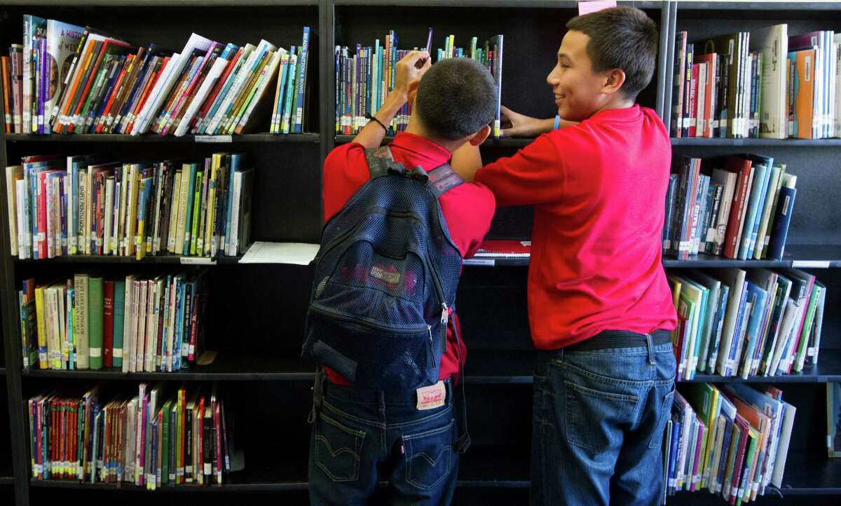 Hogg Middle School eighth-graders Sebastian Granados, left, and Ruben Alvarez, peruse books in the recently updated library.