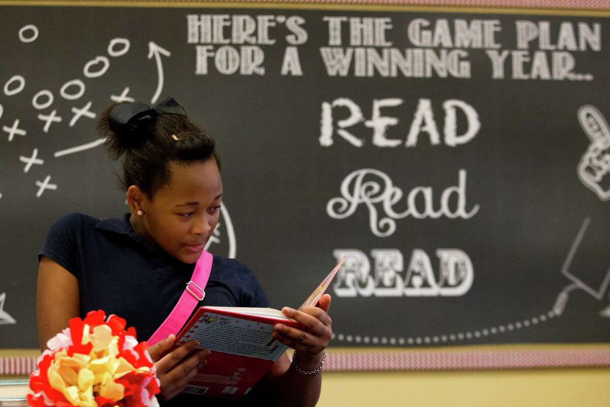 """Hogg Middle School sixth-grader Meisha Washington reads a book last week in the newly updated school library, where a sign welcomes students to """"a place to wander and wonder, a place to seek and explore."""""""