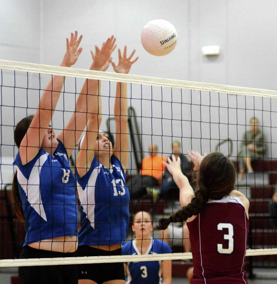 Brookfield High Schools Kim Reilly, Left, and Brianna Pirre, center, block a shot against Bethel High schools Brett Bohman, right, during a volleyball game at Bethel on Monday Oct. 7, 2013. Photo: Lisa Weir