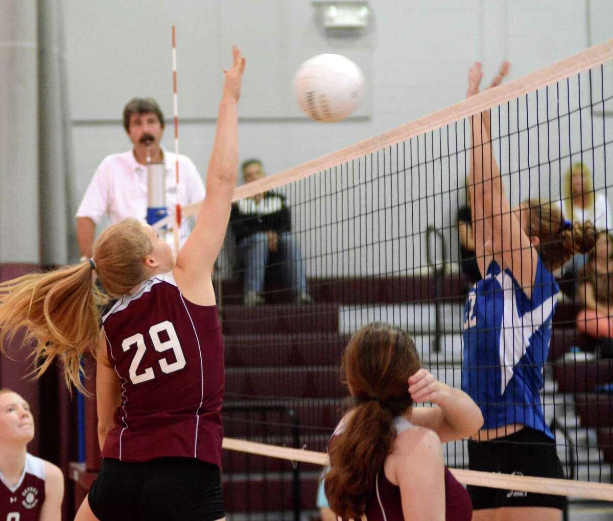 Bethel High Schools Morgan Schmid, left, reaches to block a shot against Brookfields Carolyn Marron during a volleyball game at Bethel on Monday Oct. 7, 2013.