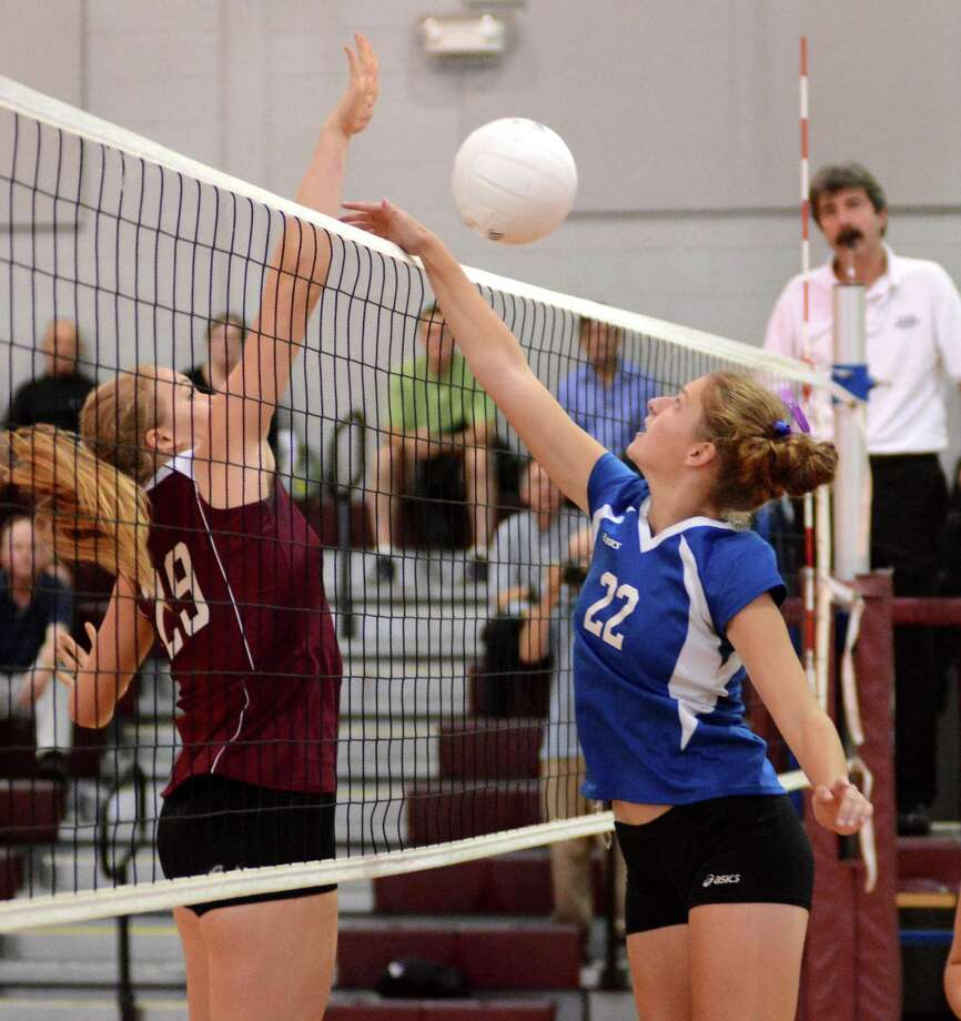 Bethel High Schools Morgan Schmid, left, reaches to block a shot against Brookfields Carolyn Marron during a volleyball game at Bethel on Monday Oct. 7, 2013. Photo: Lisa Weir / The News-Times Freelance