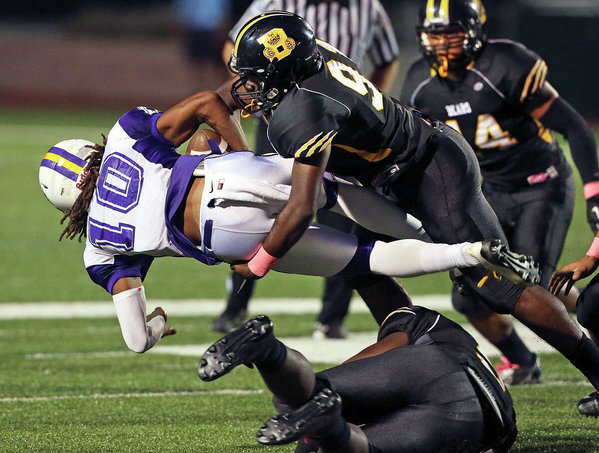Ervin Jackson does the honors after his defensive teammates hunt down Eagle quarterback Ramon Richards who can't get running room on a keeper as Brennan hosts Brackenridge at Farris Stadium on October 5, 2013.