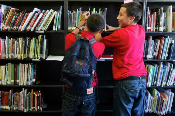 Hogg Middle School 8th graders Sebastian Granados, left, and Ruben Alvarez, look through books in the newly reopened school library on Friday, Oct. 4, 2013, in Houston. Hogg Middle School recently updated its library and hired Suzanne Webb as the new librarian after enduring budget cuts two years ago.