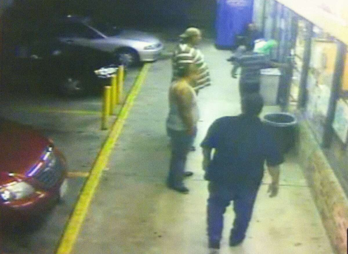 """This security camera still shows Juan Romero attempting to go back inside Diamond Food Mart as he is surrounded by attackers identified by prosecutors as Bernardo """"Tiny"""" Crisanto, top left, Jose Velez, center, and Larry Castro, foreground."""