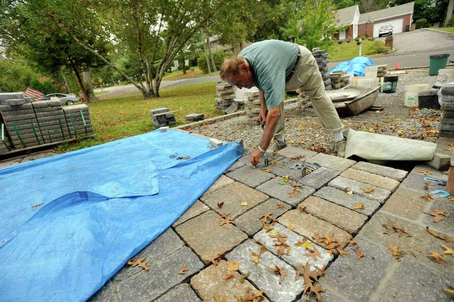 Frank Romano puts in spacers between stones for where the mortar goes in the driveway he and his wife, Filomena, are constructing outside their home in Stamford, Conn., on Monday Oct. 7, 2013. Photo: Jason Rearick / Stamford Advocate