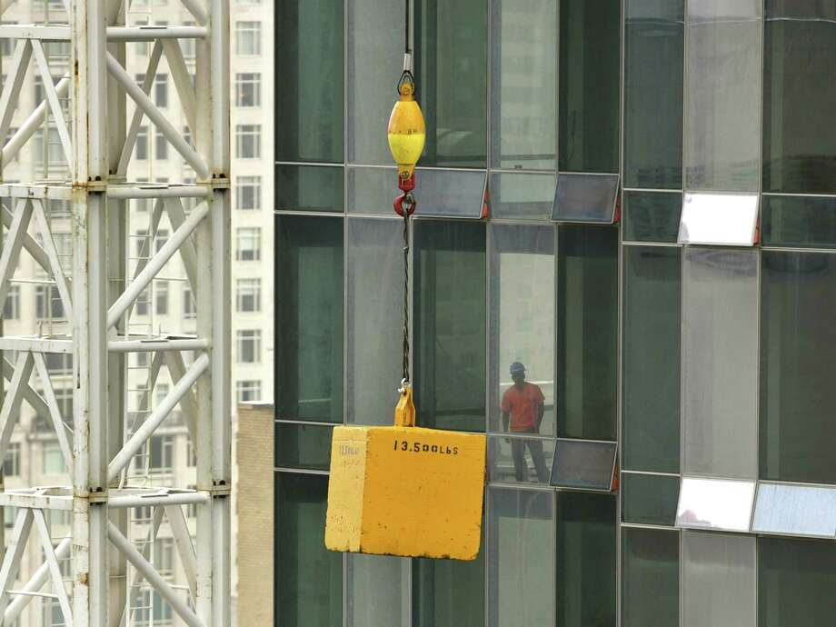 A worker looks at a box hanging from a construction crane stuck 20 stories above 57th street at the One57 building in New York on October 7, 2013. Authorities have closed West 57th Street between 6th and 7th avenues in Manhattan after a tower crane, at the same location where a crane collapsed during Superstorm Sandy was hoisting a load when it apparently got stuck     AFP PHOTO / TIMOTHY CLARYTIMOTHY CLARY/AFP/Getty Images Photo: TIMOTHY CLARY / AFP