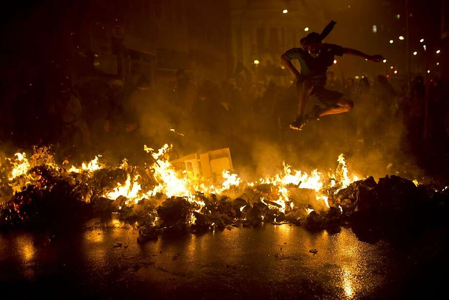 A demonstrator with his face covered jumps over a burning barricade at the Cinelandia square during a march in support of teachers on strike in Rio de Janeiro, Brazil, Monday, Oct. 7, 2013. Teachers have been on strike demanding better pay for almost two months. (AP Photo/Felipe Dana) Photo: Felipe Dana, Associated Press