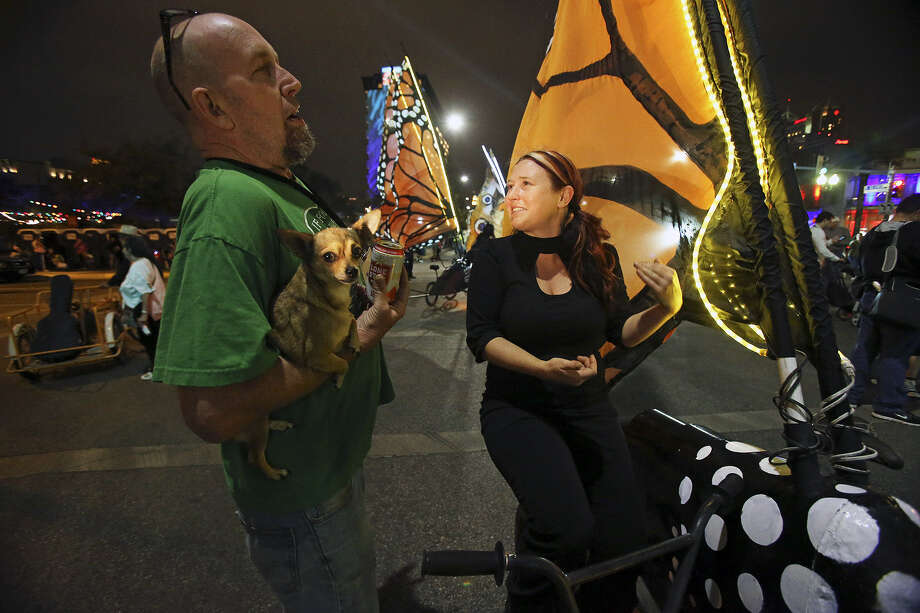 Joe Haden holds his dog Mrs. Jones as he talks with Alisha Cloud during Luminaria in March. Two event board members say Luminaria likely will move to November as early as next year. Photo: San Antonio Express-News File Photo