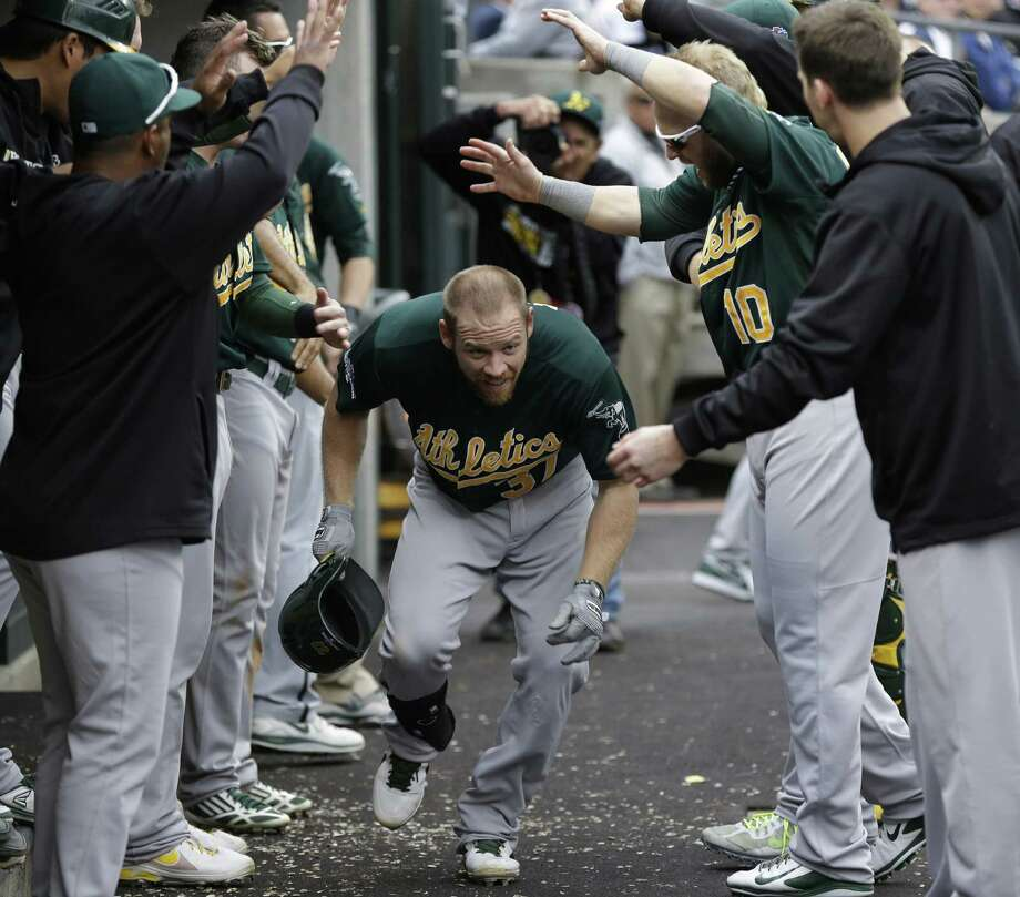 The A's cheer Brandon Moss after his solo home run broke a 3-all tie in the fifth inning in Detroit. Photo: Paul Sancya / Associated Press