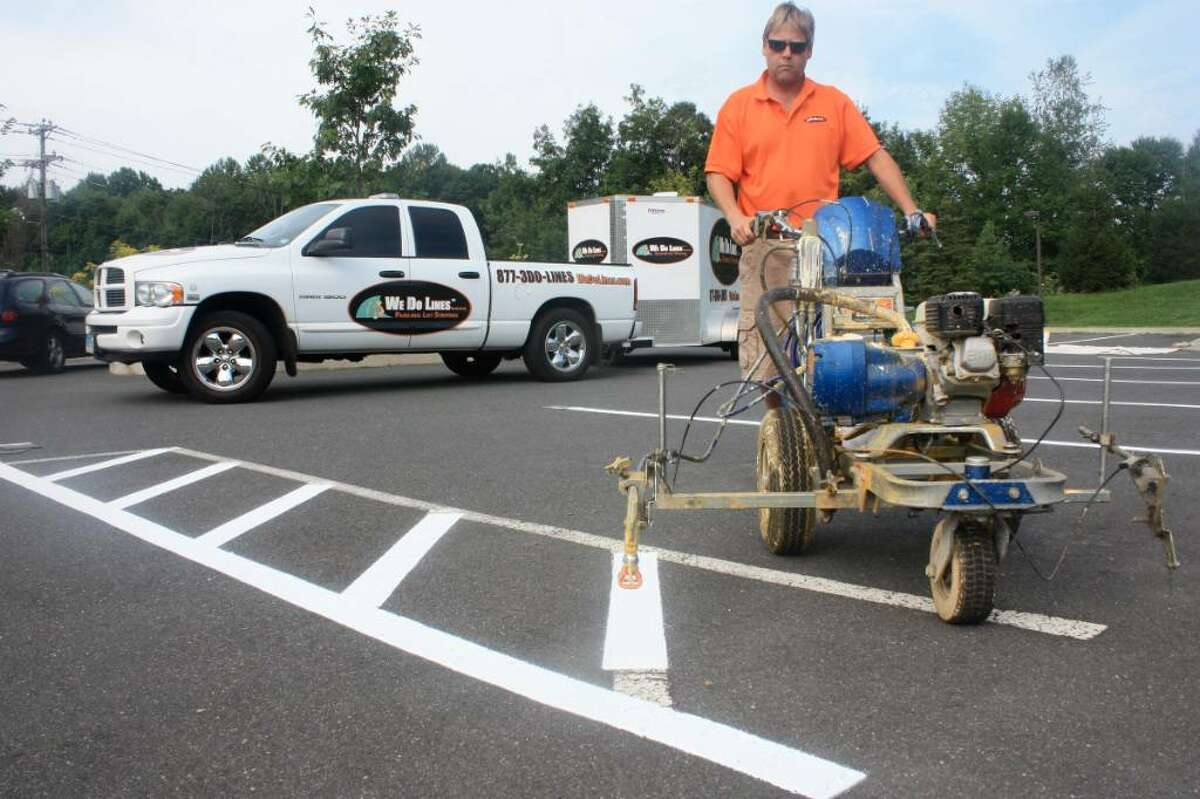 Ridgefield native Tom Darrow maneuvers a line-painter. He is a founder of We Do Lines, a Ridgefield-based line-painting company he and three friends founded in 2008 that has quickly grown to stripe about 60 parking lots a month up and down the East Coast. They are offering franchise opportunities to others who want to do lines.