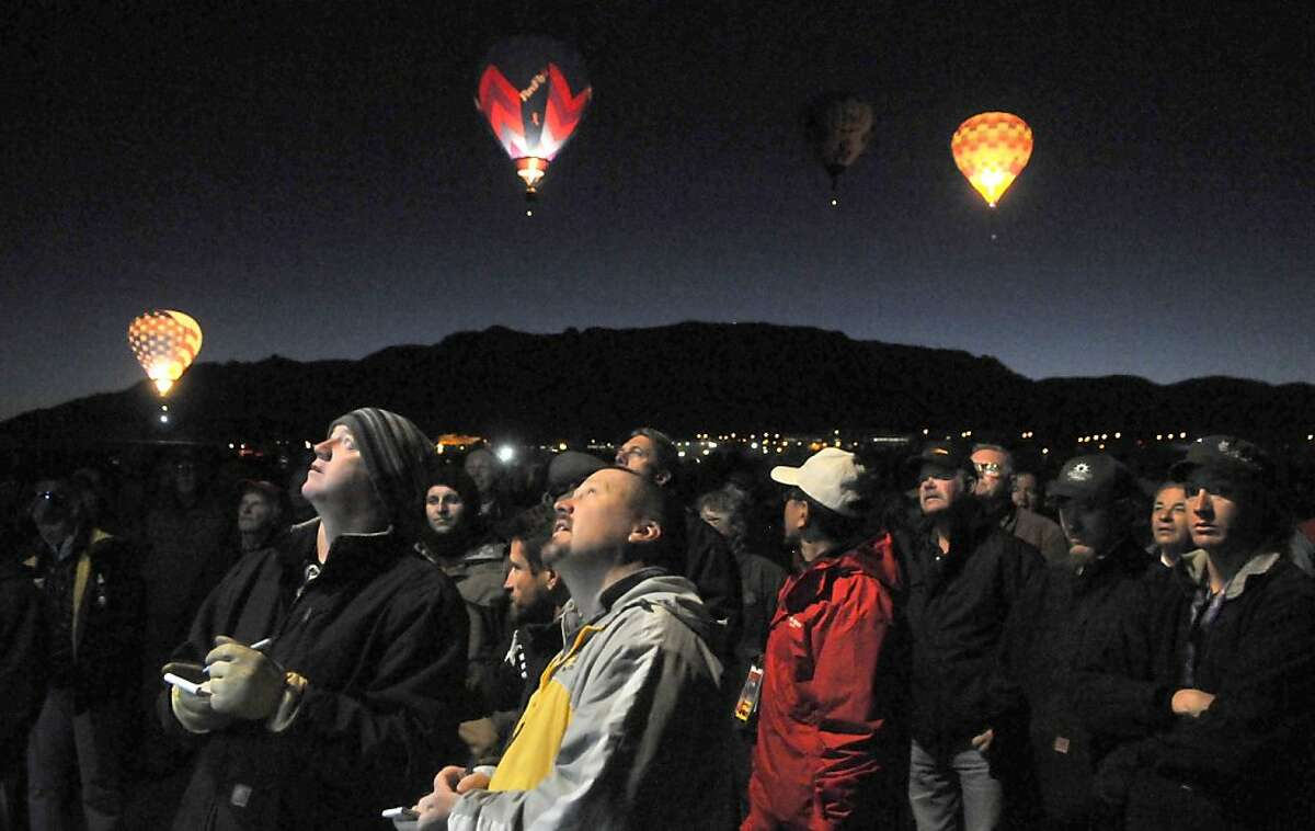 The Dawn Patrol floats overhead as pilots, including Jeff Hooten of Albuquerque, left, and Bruce Wood of Carbondale, Colo., center, listen during the pilots briefing at the Albuquerque International Balloon Fiesta on Monday, October 7, 2013. (AP Photo/The Albuquerque Journal, Greg Sorber) THE SANTA FE NEW MEXICAN OUT