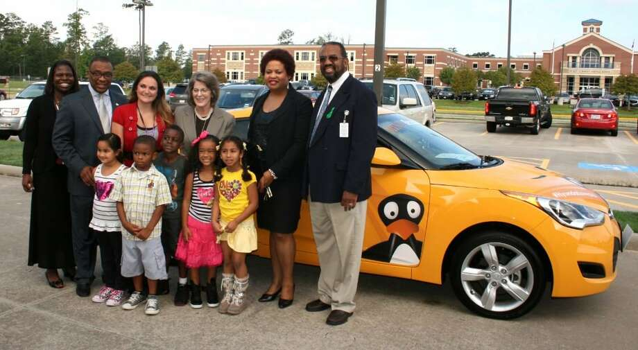 A new Hyundai Veloster with the logo of JiJi, ST Math?s popular penguin, is the backdrop for a group photo following the official launch of the ST Math program at Burchett Elementary School. Back row, from right, are Spring ISD Secondary Mathematics Direc Photo: Photo Provided