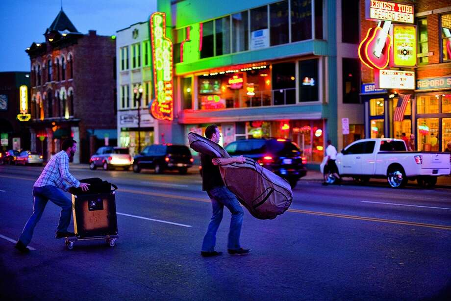 SPRING | Nashville, TennesseeMusicians muscle their instruments across Nashville'€™s Broadway, likely bound for one of the world-famous honky-tonks that line €œLower Broad.  (From National Geographic's 'Four Seasons of Travel') Photo: Will Van Overbeek, National Geographic Stock