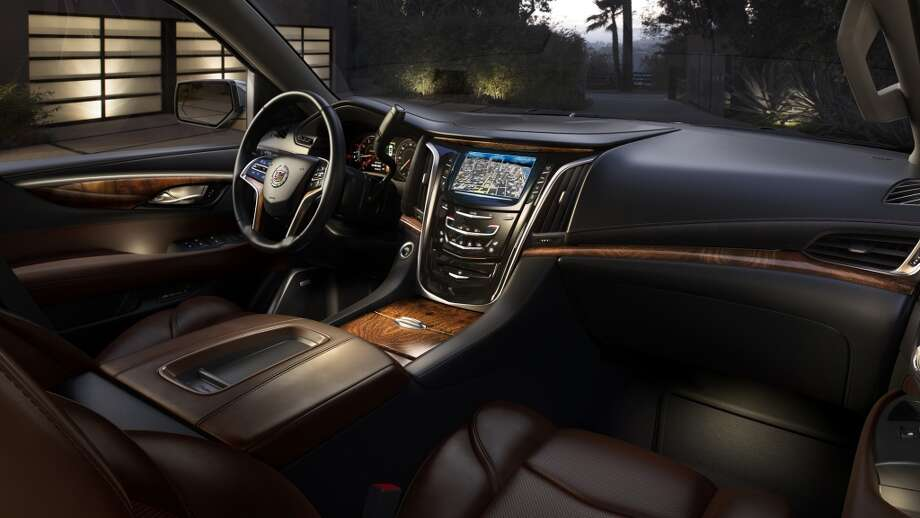 The 2015 Cadillac Escalade's all-new interior combines luxurious handcrafted elements, shown here in Kona/Ebony with elm cluster open-pore wood trim.