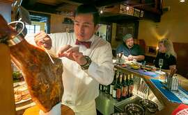 Bartender Eduardo Celaya slices ham during Happy Hour at Iberia restaurant in Menlo Park, Calif., on Tuesday, September17th, 2013.