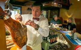 Bartender Eduardo Celaya slices ham during Happy Hour at Iberia restaurant in Menlo Park, Calif., on Tuesday, September17th, 2013.