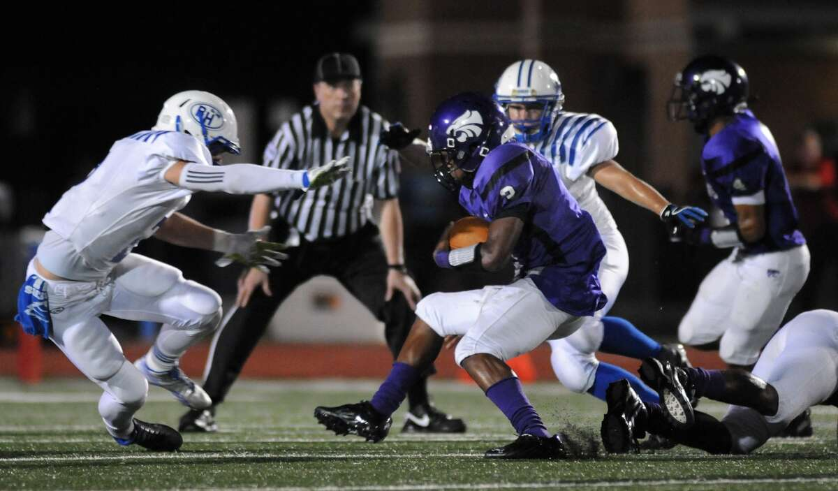 Humble running back Deneric Gibson, center, tries to escape a pair of Barbers Hill defenders during a game at Turner Stadium. Gibson leads the ground attack for the Wildcats with 330 yards and three touchdowns.