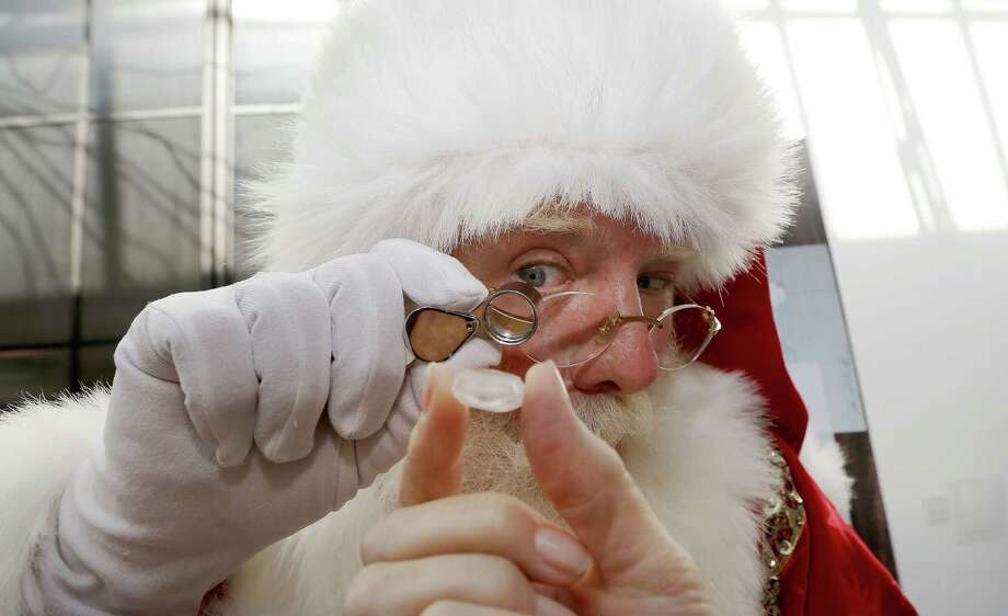 Actor Brady White portrays Santa Claus as he looks at a 25-carat rough Forevermark diamond  offered in the Neiman Marcus Christmas Book Tuesday, Oct. 8, 2013, in Dallas.  The Forevermark Ulitmate Diamond Experience on sale for $1,850,000 includes a rough diamond and a trip to London and Africa to trace the provenance of the stone.  (AP Photo/LM Otero) ORG XMIT: TXMO104 Photo: LM Otero / AP