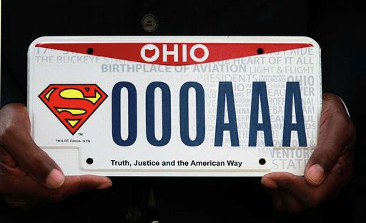 """State representative Bill Patmon holds the new Superman license plate that will be available from the Bureau of Motor Vehicles on Oct. 7, 2013 in Cleveland. Ohio fans of the Man of Steel now officially can have the Superman logo on their wheels. A license plate with the iconic """"S'' insignia and the phrase """"Truth, Justice and the American Way"""" went on sale Monday. Relatives of Superman creators Jerry Siegel and Joe Shuster were on hand for the plate's unveiling outside the Cleveland-area home where Siegel lived, The plates cost $20, plus the standard registration fee of $34.50 or the typical $16.25 in fees to replace existing plates. Part of the fee goes to the Siegel and Shuster Society, which commemorates the men's work. Patmon was responsible for introducing legislation for the license plate in the Ohio House. (AP Photo/The Plain Dealer, Gus Chan)"""